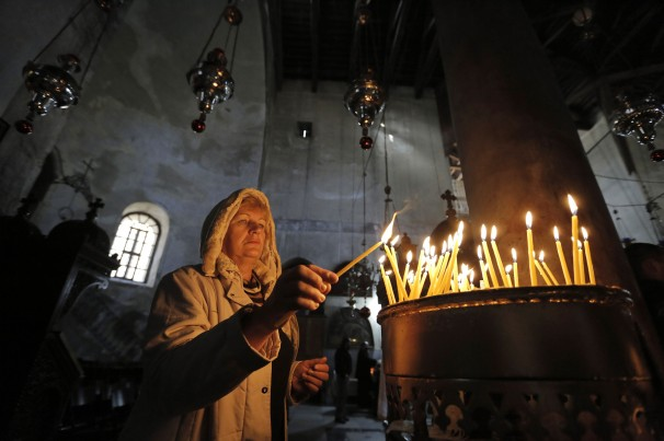 Aworshipper lights candles at Bethlehem's Church of the Nativity.