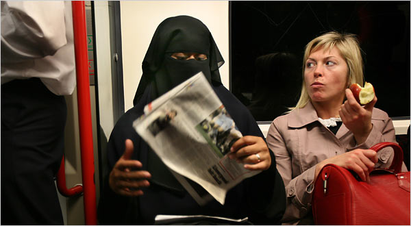 Below, a burqa person takes public transit in Britain as a western woman looks on.