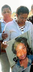Charlene Lovett holding photo of daughter Cheryl Green
